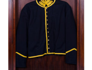 A Civil War uniform jacket displayed and protected in our solid mahogany uniform display case