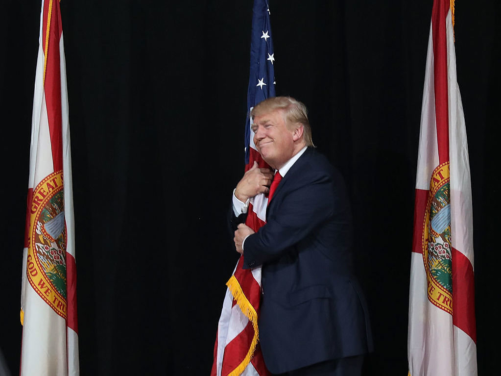 Donald Trump hugs the American flag at a Florida campaign rally in October 2016.
